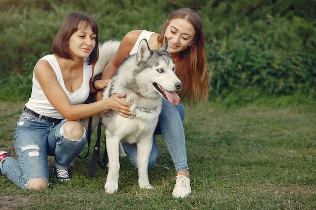 Zwei frauen in einem frühlingspark, der mit nettem hund spielt