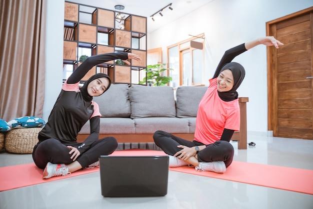 Zwei frauen in hijab-sportbekleidung sitzen mit gekreuzten beinen auf dem boden. ihre körper sind zur seite gelehnt und die hände hoch, während sie gemeinsam ihre arme im haus aufwärmen
