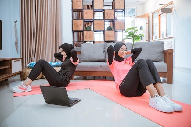 Zwei frauen in hijab-sportkleidung machen sit-ups, um die bauchmuskeln vor einem laptop zu trainieren, während sie zusammen im haus unterwegs sind