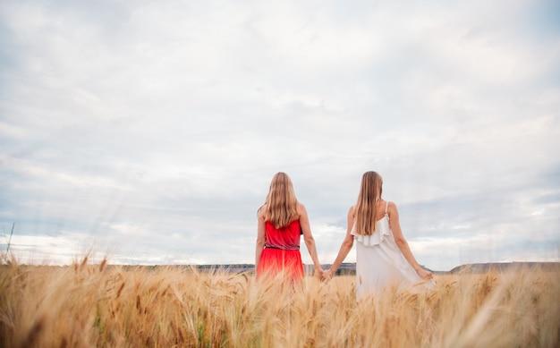 Zwei frauen in kleidern auf einem weizenfeld