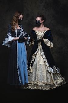 Zwei frauen in renaissance-kleid, gesichtsmaske und handschuhen, coronavirus, covid-19-schutzkonzept.