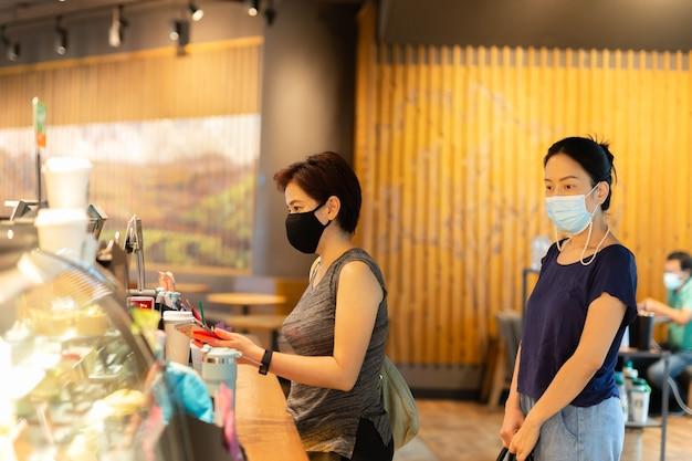Zwei frauen in schutzmaske kaufen kaffee im café coffee
