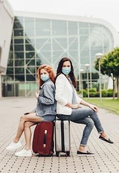 Zwei frauen in schutzmasken sitzen auf koffern und warten auf den flug.