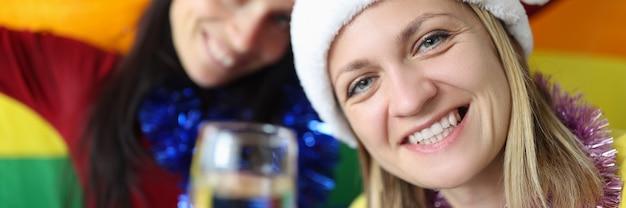 Zwei frauen in weihnachtsmann-hüten trinken champagner und halten die lgbt-flagge