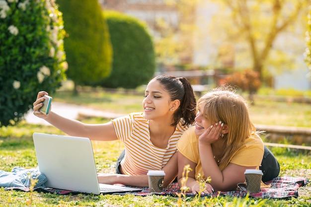 Zwei frauen latina im park liegend auf einer decke mit computer und kaffee, die an einem sonnigen tag ein selfie machen