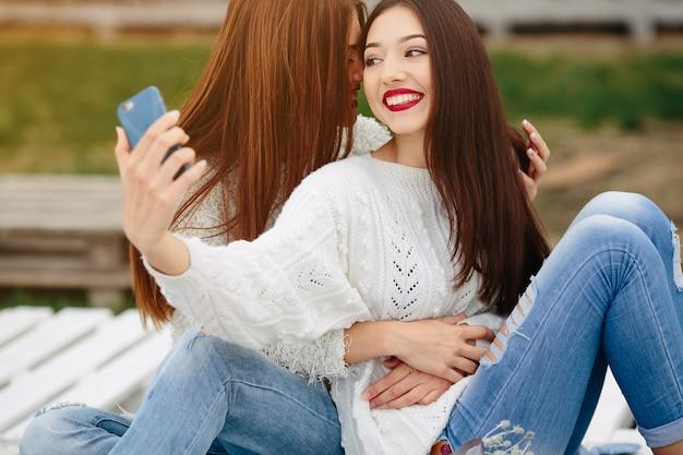 Zwei frauen machen selfie auf der bank im park