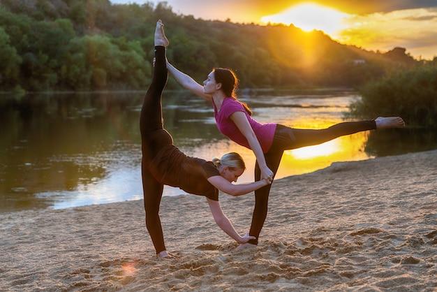Zwei frauen machen synchronisiertes akrobatik-yoga