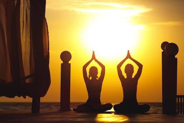 Zwei frauen machen yoga bei sonnenaufgang am meer