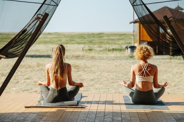Zwei frauen meditieren auf der türschwelle eines großen zeltes, von hinten. in einfacher pose sitzen und yoga machen. rundherum schöne ebene steppe. anti-moskitonetz hängt an den seiten wie vorhänge.