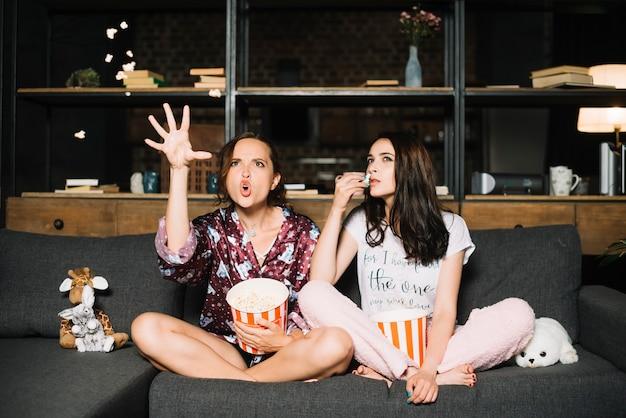 Zwei frauen mit dem popcorn, der horrorfilm aufpasst