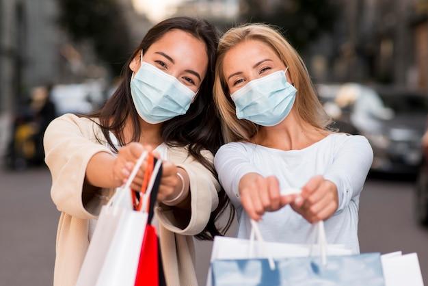 Zwei frauen mit medizinischen masken, die zusammen mit einkaufstaschen aufwerfen