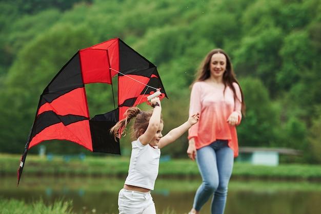 Zwei frauen. positives kind und ihre mutter laufen mit rotem und schwarzem drachen in den händen im freien