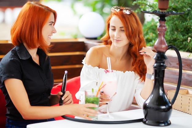 Zwei frauen rauchen eine wasserpfeife und genießen cocktails in einem café auf der straße