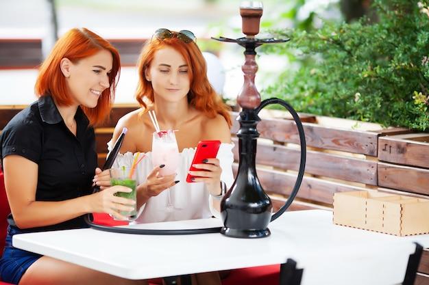 Zwei frauen rauchen eine wasserpfeife und genießen cocktails in einem café auf der straße.