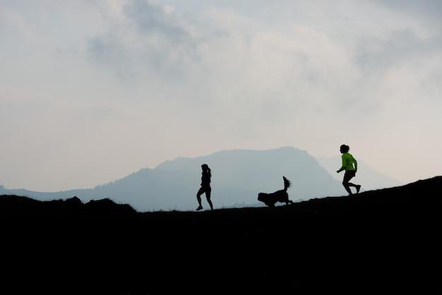 Zwei frauen rennen mit einem hund in den bergen