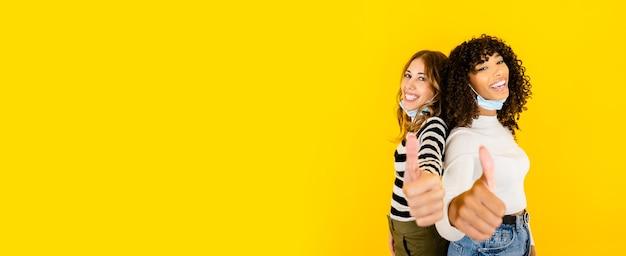Zwei frauen schwarzer hispanic und kaukasier mit medizinischer maske unten, die kamera mit den daumen oben auf großem gelbem kopienraum schauend