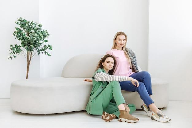 Zwei frauen sitzen auf der couch und schauen in die kamera