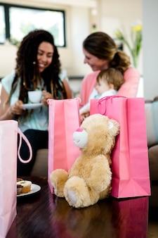 Zwei frauen sitzen auf einer couch mit einem baby, umgeben von geschenken