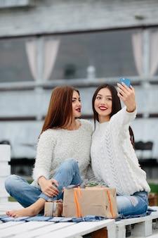 Zwei frauen sitzen draußen auf einer bank und schießen geschenke für das smartphone