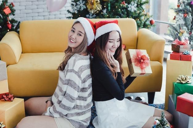 Zwei frauen sitzen hintereinander und halten geschenkboxen mit fröhlichem lächeln zu hause beim weihnachtsfest zusammen.