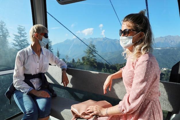 Zwei frauen sitzen in einer gläsernen kabinenseilbahn in gesichtsmasken und sozialer distanz