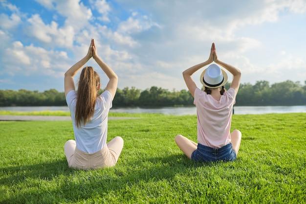 Zwei frauen sitzen in lotussitz auf grünem gras