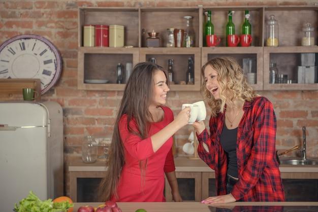 Zwei frauen trinken kaffee in der küche