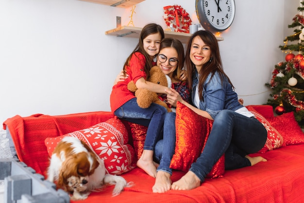 Zwei frauen und ein kleines mädchen mit einem hund haben spaß auf der couch in der nähe des weihnachtsbaumes zu hause