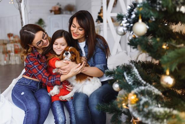 Zwei frauen und ein mädchen mit einem hund haben spaß in der nähe des weihnachtsbaumes in den weihnachtsferien.