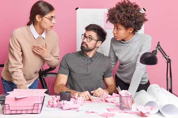 Zwei frauen und ein mann kollegen posieren im coworking space diskutieren ideen für ein zukünftiges ingenieurprojekt haben verwirrte ausdrücke kooperieren an informationen für eine gemeinsame aufgabe. teambuilding und partnerschaft