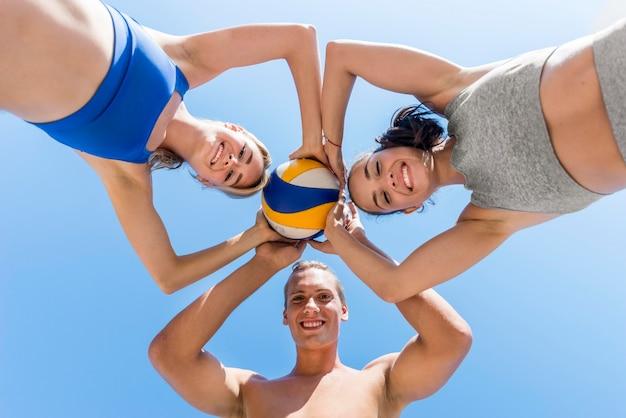 Zwei frauen und ein mann posieren zusammen mit volleyball