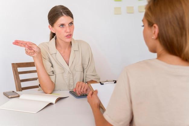 Zwei frauen unterhalten sich am tisch mit gebärdensprache