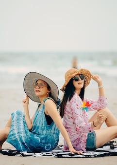 Zwei frauen, welche die strandentspannung froh im sommer durch tropisches blaues wasser genießen. modell auf tragendem strandhut der reise.