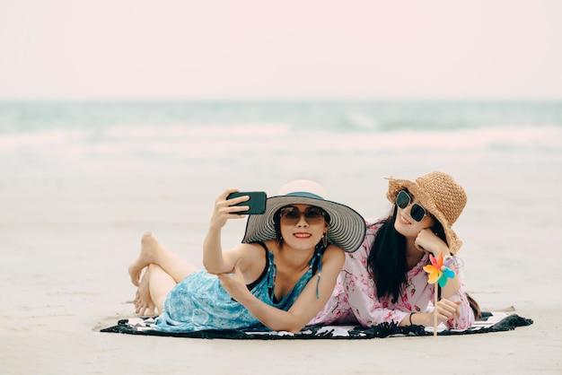 Zwei frauen, welche die strandentspannung froh im sommer genießen