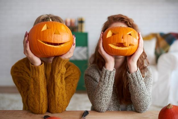 Zwei frauen zeigen halloween-kürbisse
