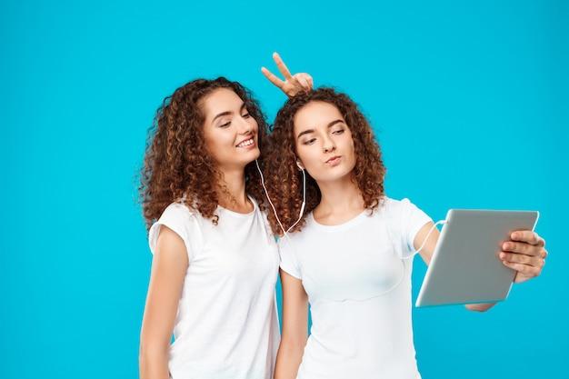 Zwei frauen zwillinge machen selfie auf tablette über blau.