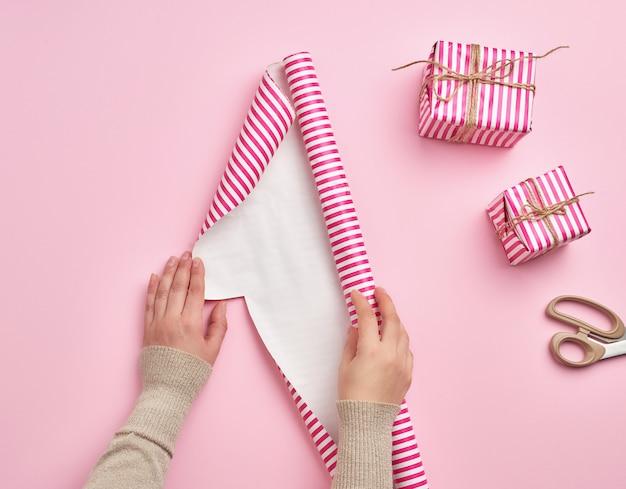 Zwei frauenhänden entfalten eine rolle geschenkpapier, neben zwei geschenken, rosa