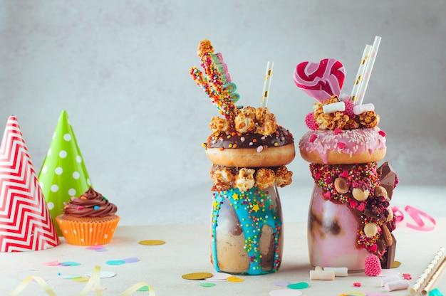 Zwei freak-shakes mit donut und süßigkeiten