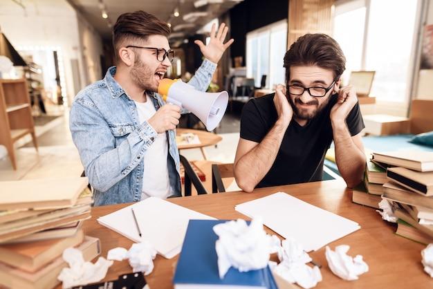 Zwei freiberufler männer arbeiten am schreibtisch, umgeben von büchern.