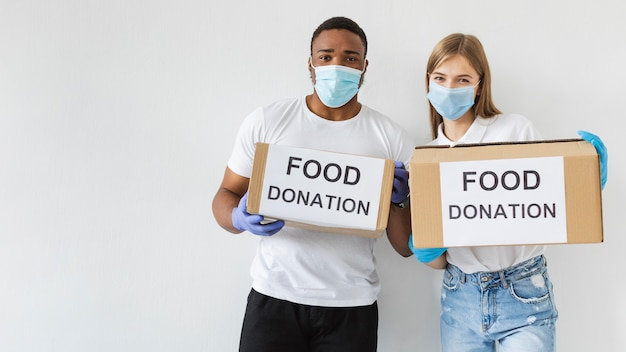 Zwei freiwillige halten spendenboxen mit kopierraum