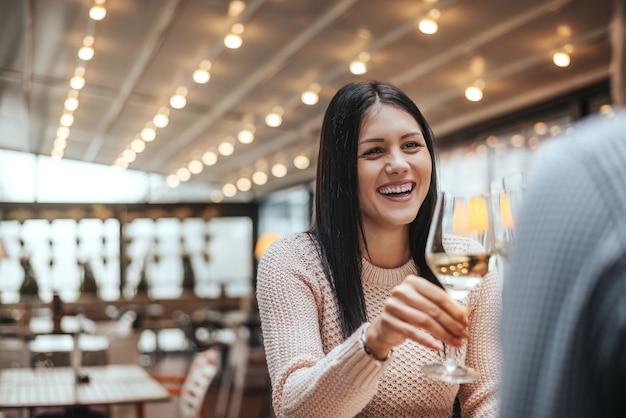 Zwei freund, der wein im caférestaurant spricht und trinkt.