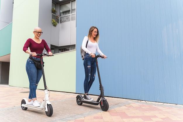 Zwei freund-mädchen, die elektrischen roller auf die bürgersteige reiten.