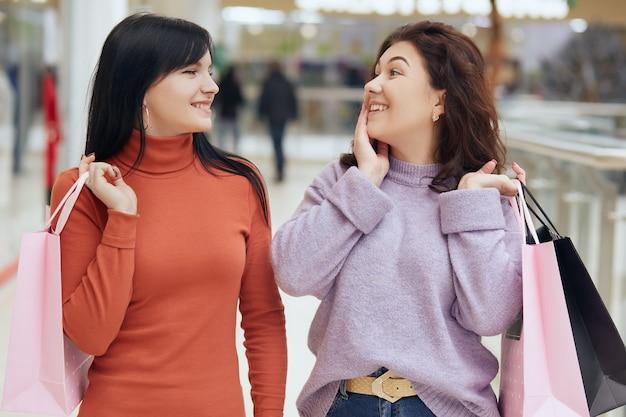 Zwei freunde beim einkaufen im einkaufszentrum posieren erstaunt und aufgeregt