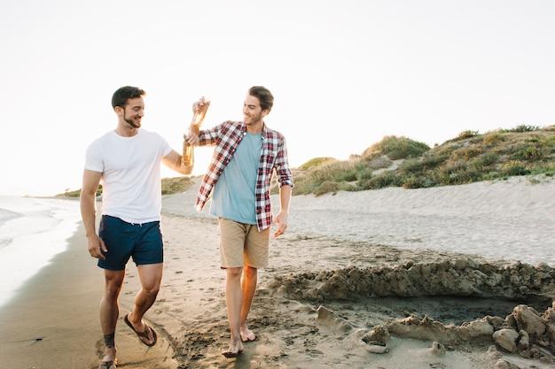 Zwei freunde, die am strand spazieren gehen