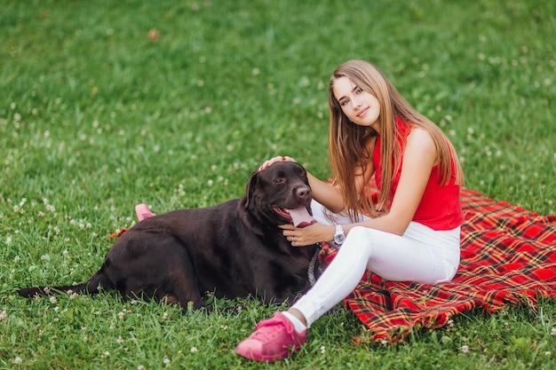 Zwei freunde, die auf dem teppich im garten liegen, blonde frau und ihr hund
