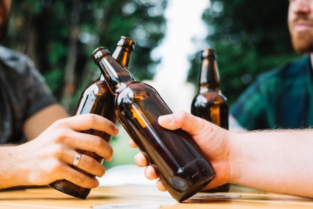 Zwei freunde, die die flaschen bier über der tabelle klirren