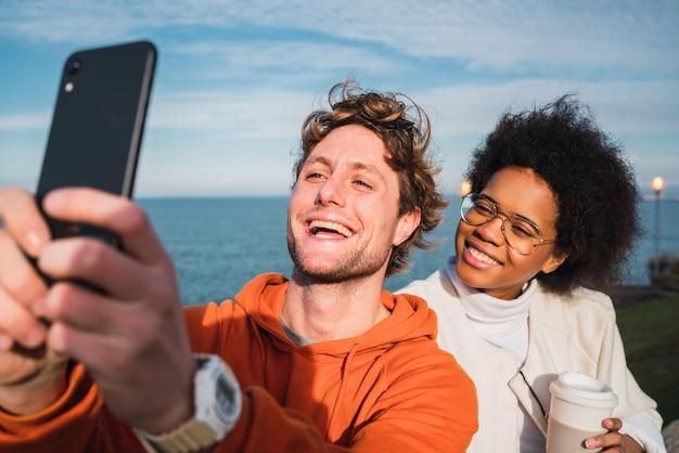 Zwei freunde, die ein selfie mit smartpone machen.