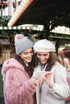 Zwei freunde, die handy auf einem weihnachtsmarkt durchsuchen