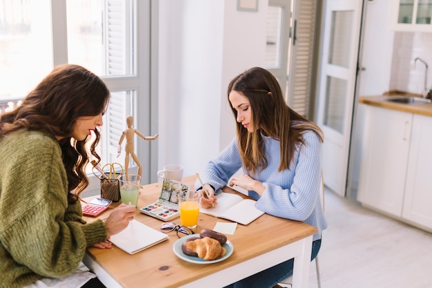 Zwei freunde, die in küche zeichnen