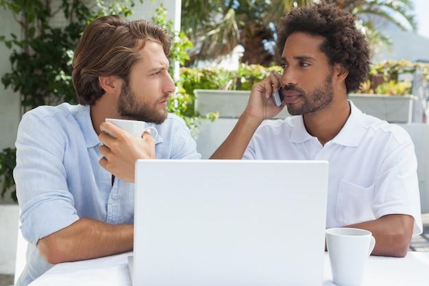 Zwei freunde, die kaffee zusammen mit laptop genießen